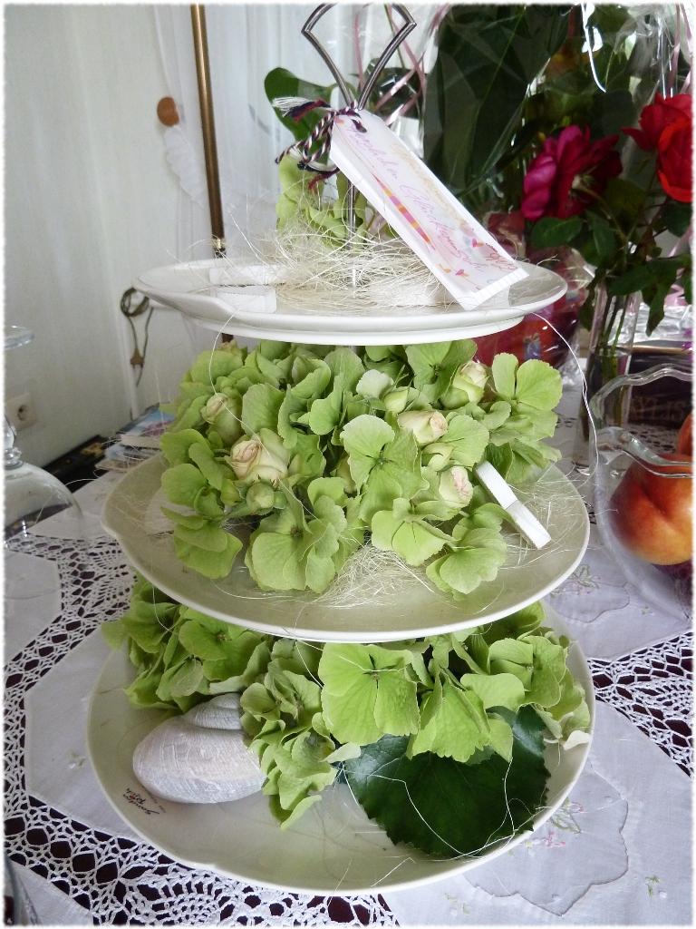 Etagere mit grünen Hortensien und weißen Rosen