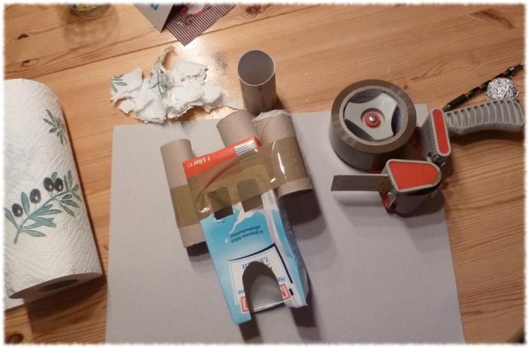 Bei einem Milchkarton die Pappe von Toilettenpapier-oder Küchenrollen mit Klebeband befestigen. Fenster und Türen in den Karton schneiden